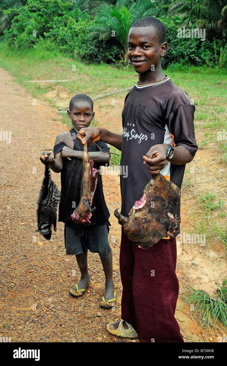 Young boys offer bushmeat for sale on side of road Liberia - Stock Image