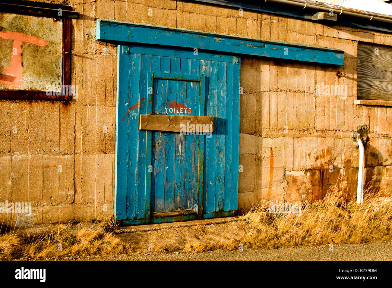 Old block toilet with blue wooden door and wooden bar across the door in Buckie, Scotland - Stock Image