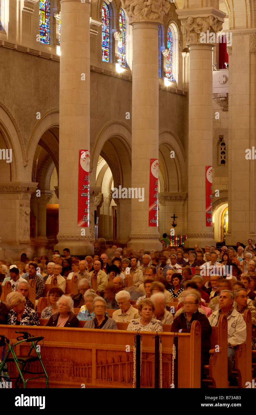 People sitting waiting for mass inside the cathedral at Ste Ane de Beaupre in Quebec - Stock Image