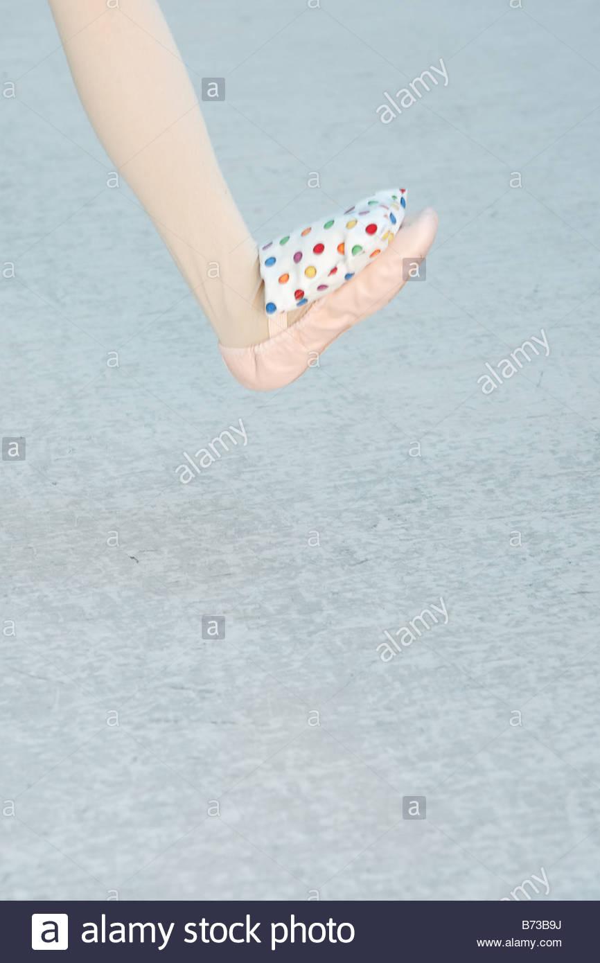 Ballerina balancing a bean bag on her ballet slipper Stock Photo