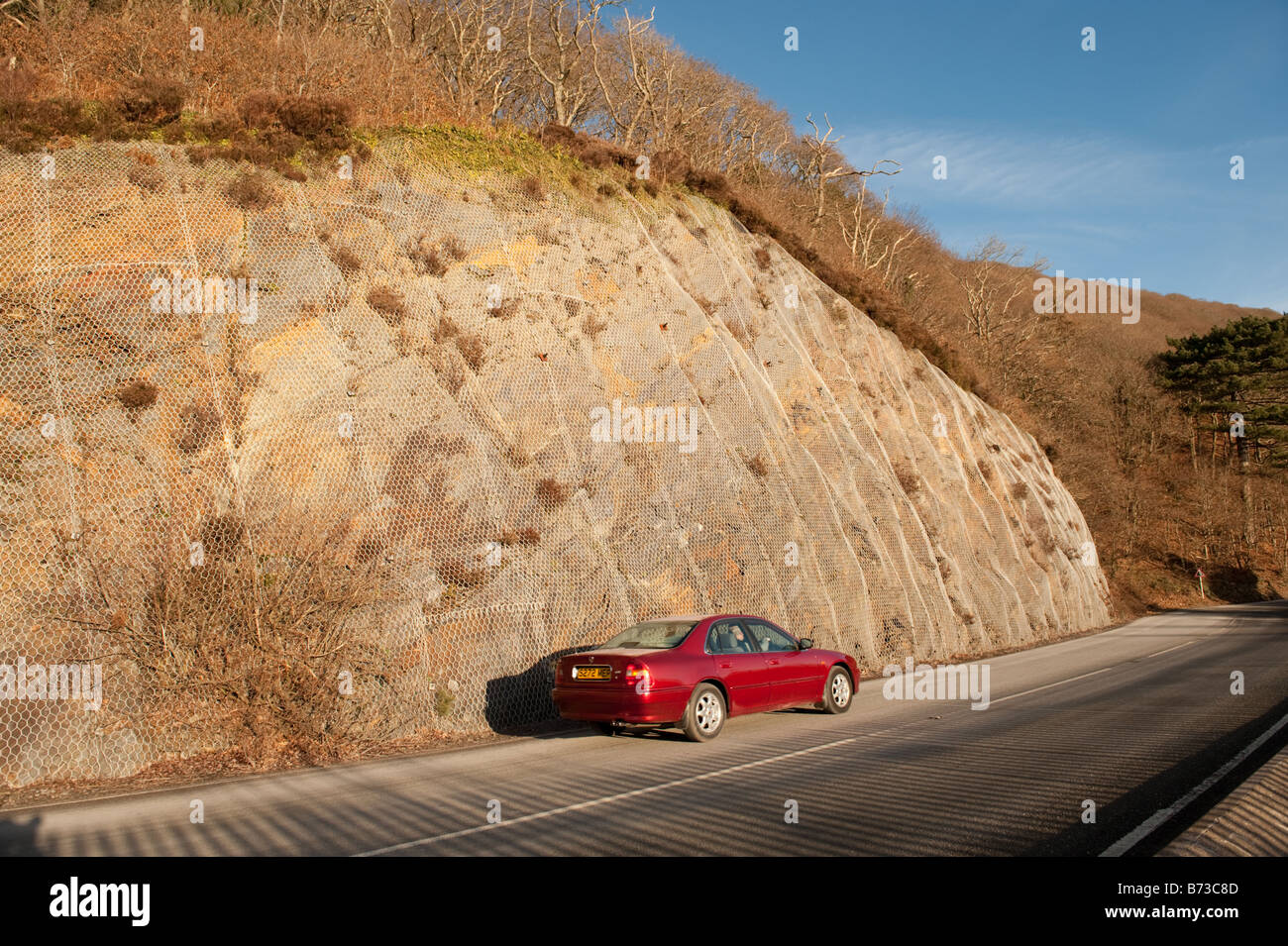 Embankment cutting contained within metal meshing to prevent loose rocks from falling on to road A493 near Aberdyfi - Stock Image