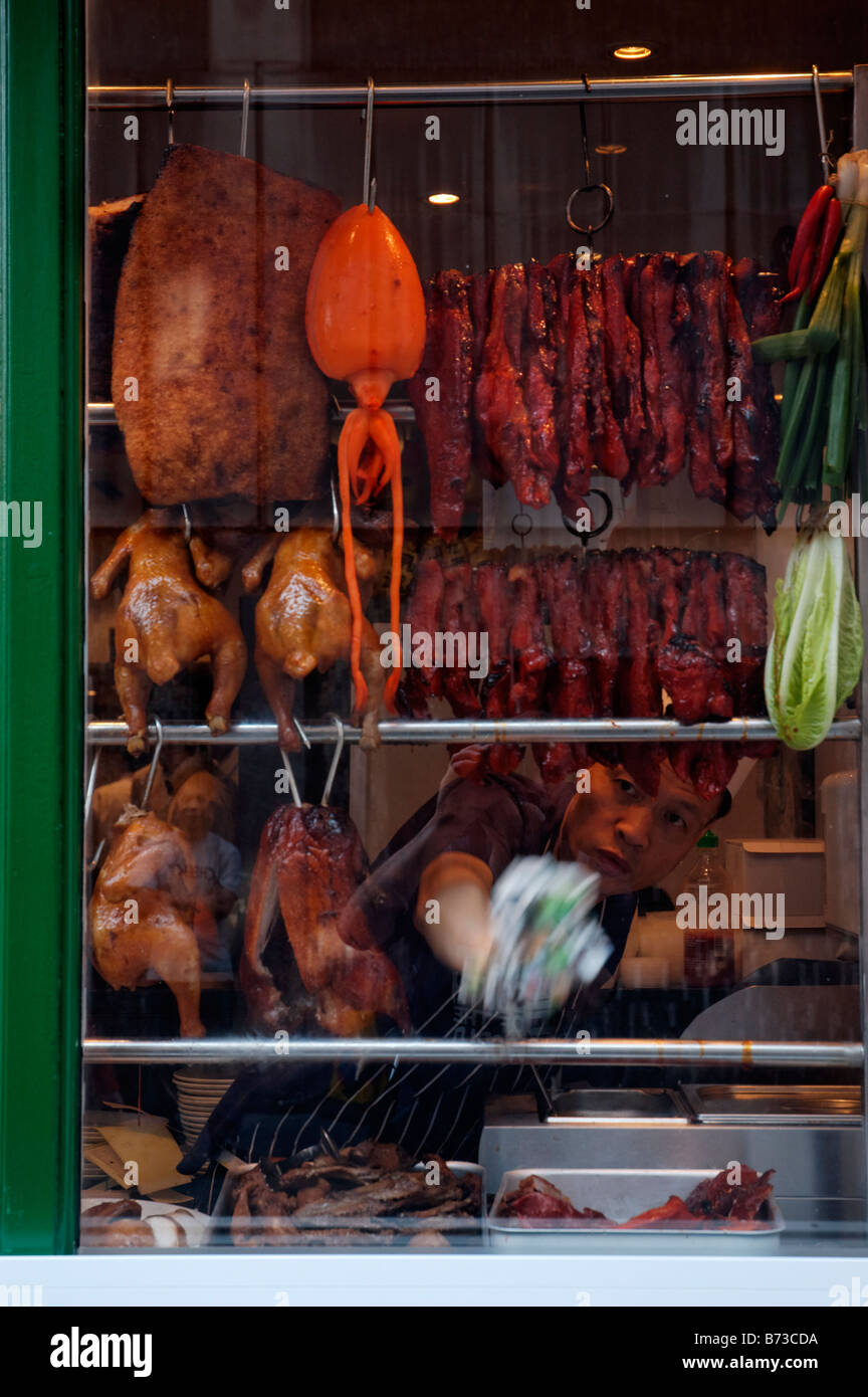 Crispy duck and squid in a window in Chinatown in London - Stock Image