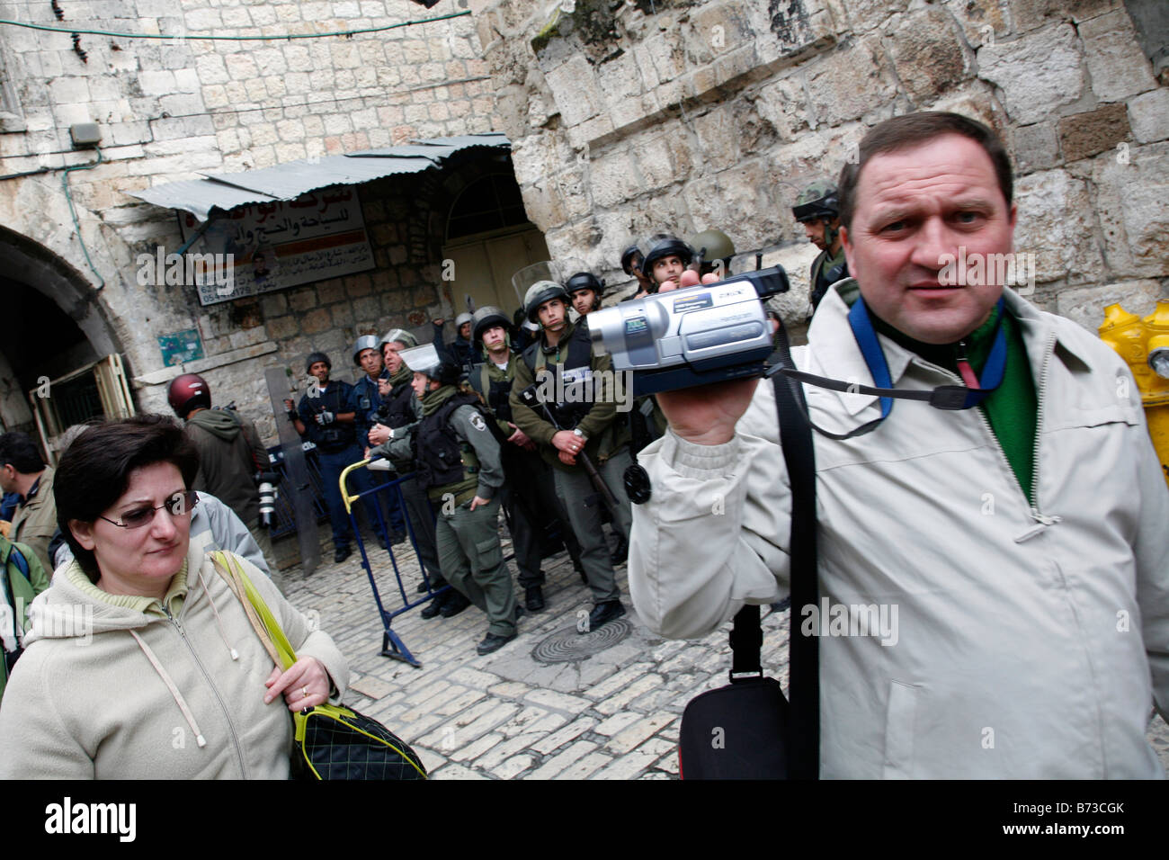 Christian tourists walking past Israeli police in the Old City of Jerusalem. - Stock Image