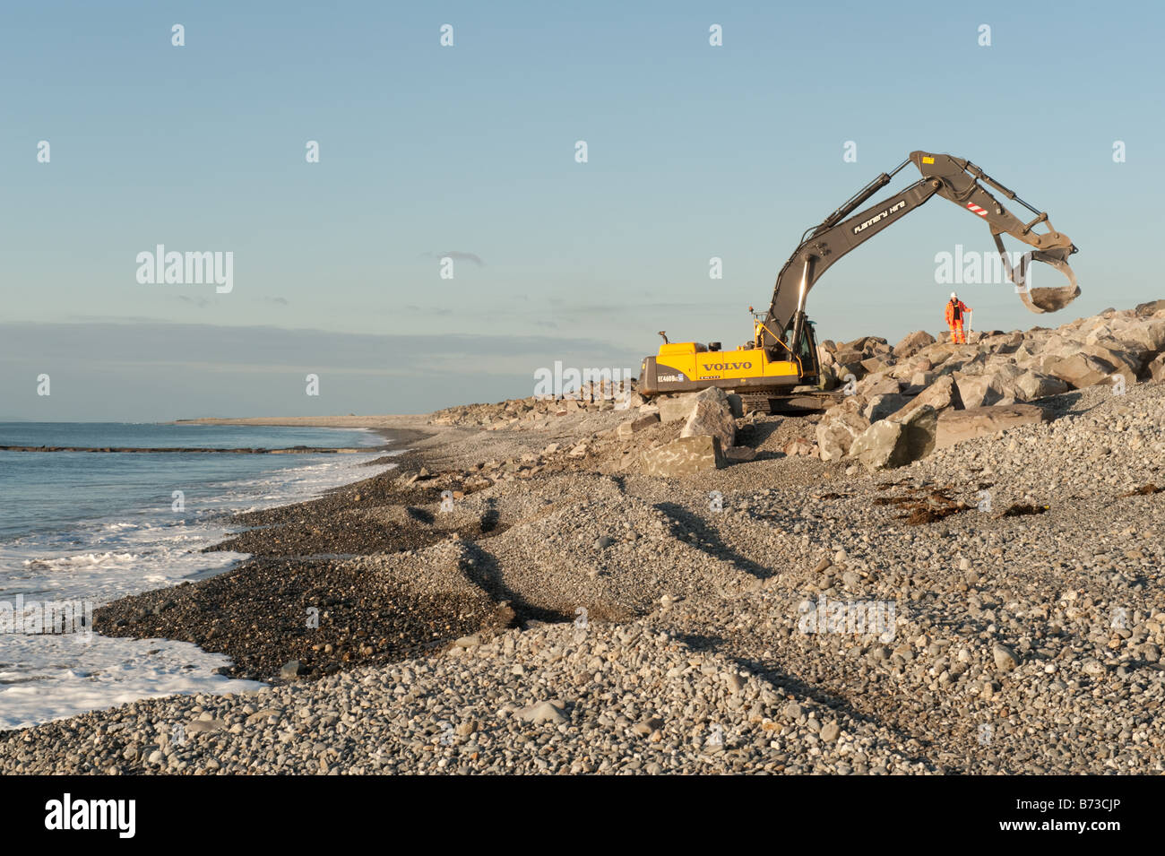 Mechanical JCB digger placing large boulders repairing the sea defences on the beach at Tywyn Gwynedd north wales - Stock Image