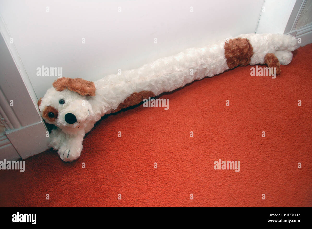 A dog shaped draft excluder lies at the base of a door. - Stock Image