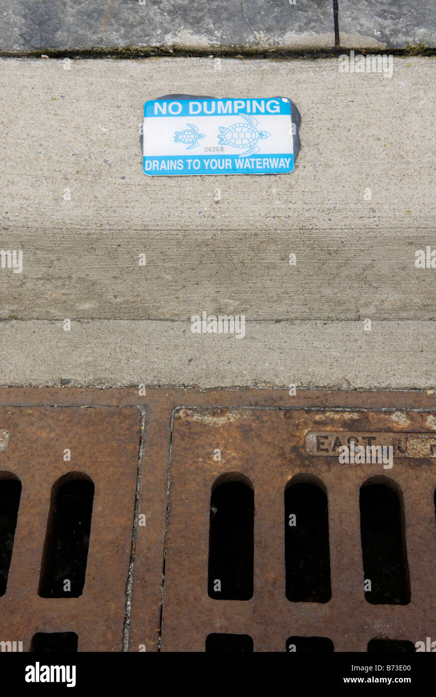 Storm drain with decal warning against pollution dumping - Stock Image