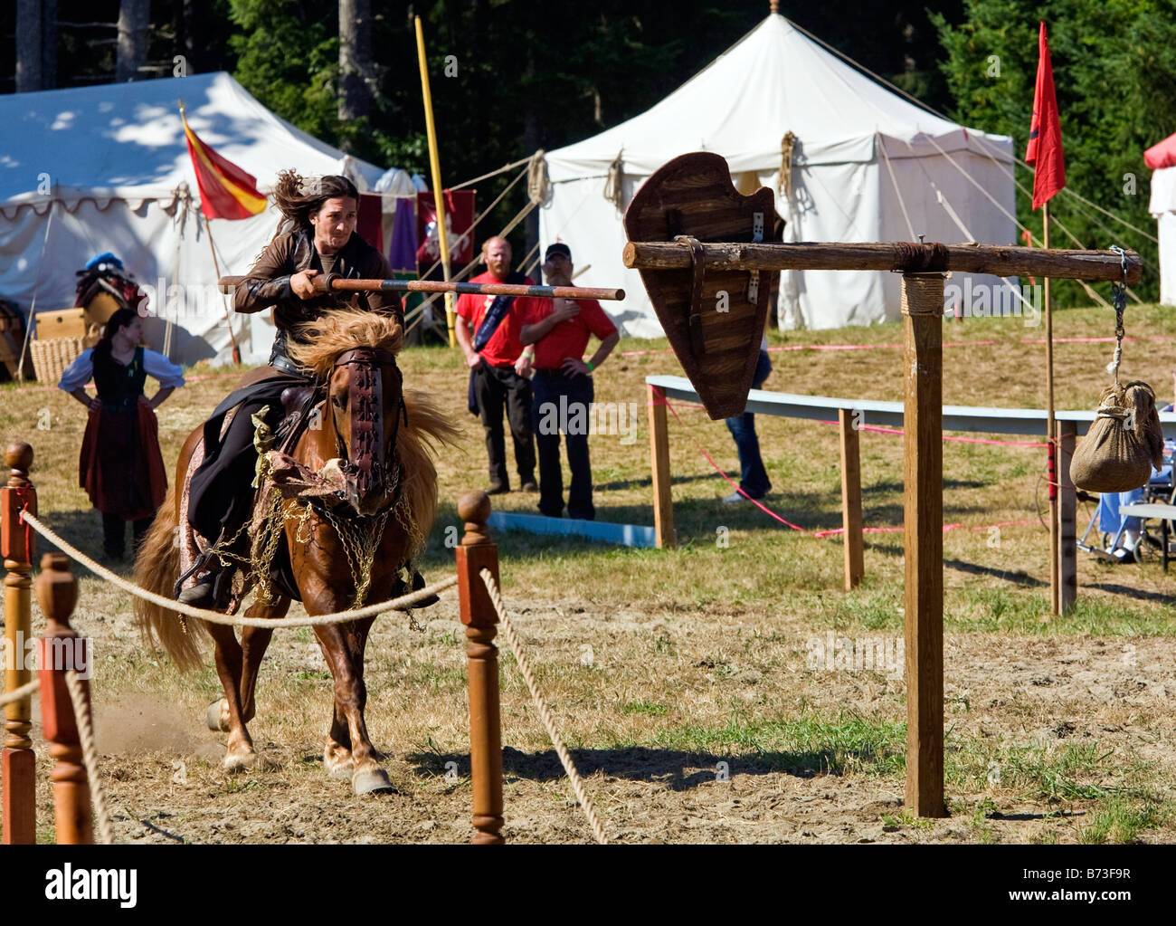 Image of man dressed in Renaissance style clothing riding a horse and carrying a lance in a jousting tournament - Stock Image