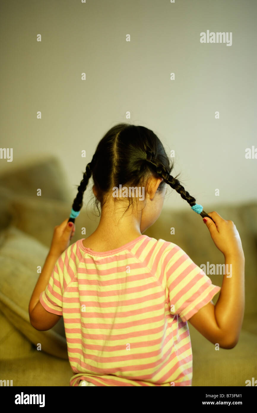 Five year old girl pulls her pigtails - Stock Image