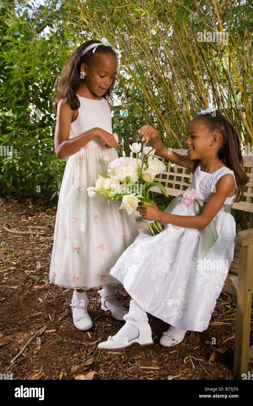 Happy African American flower girls sitting on garden bench holding ...