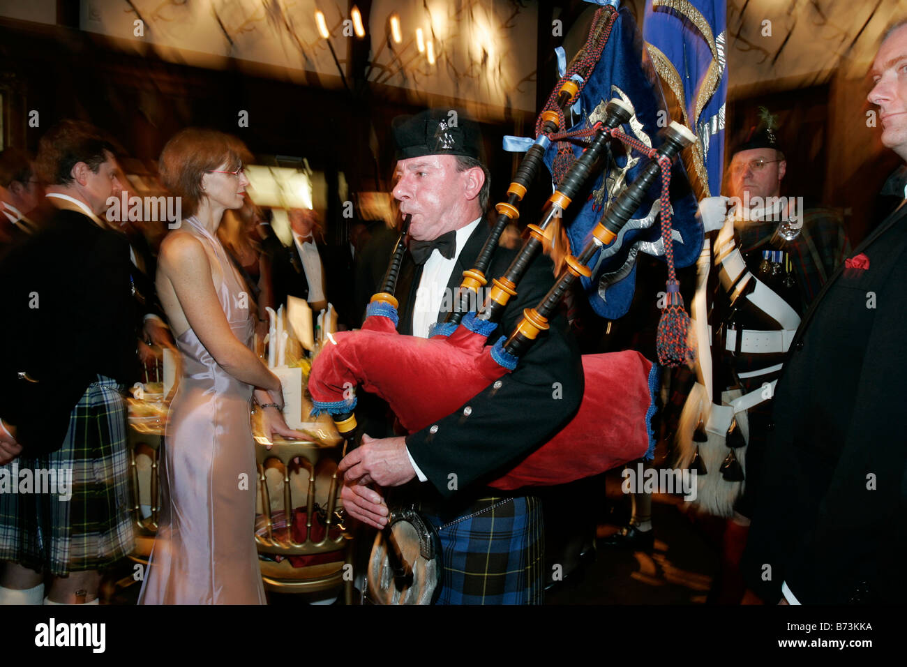 A piper leads in the guests at a traditional Burns Night supper - Stock Image