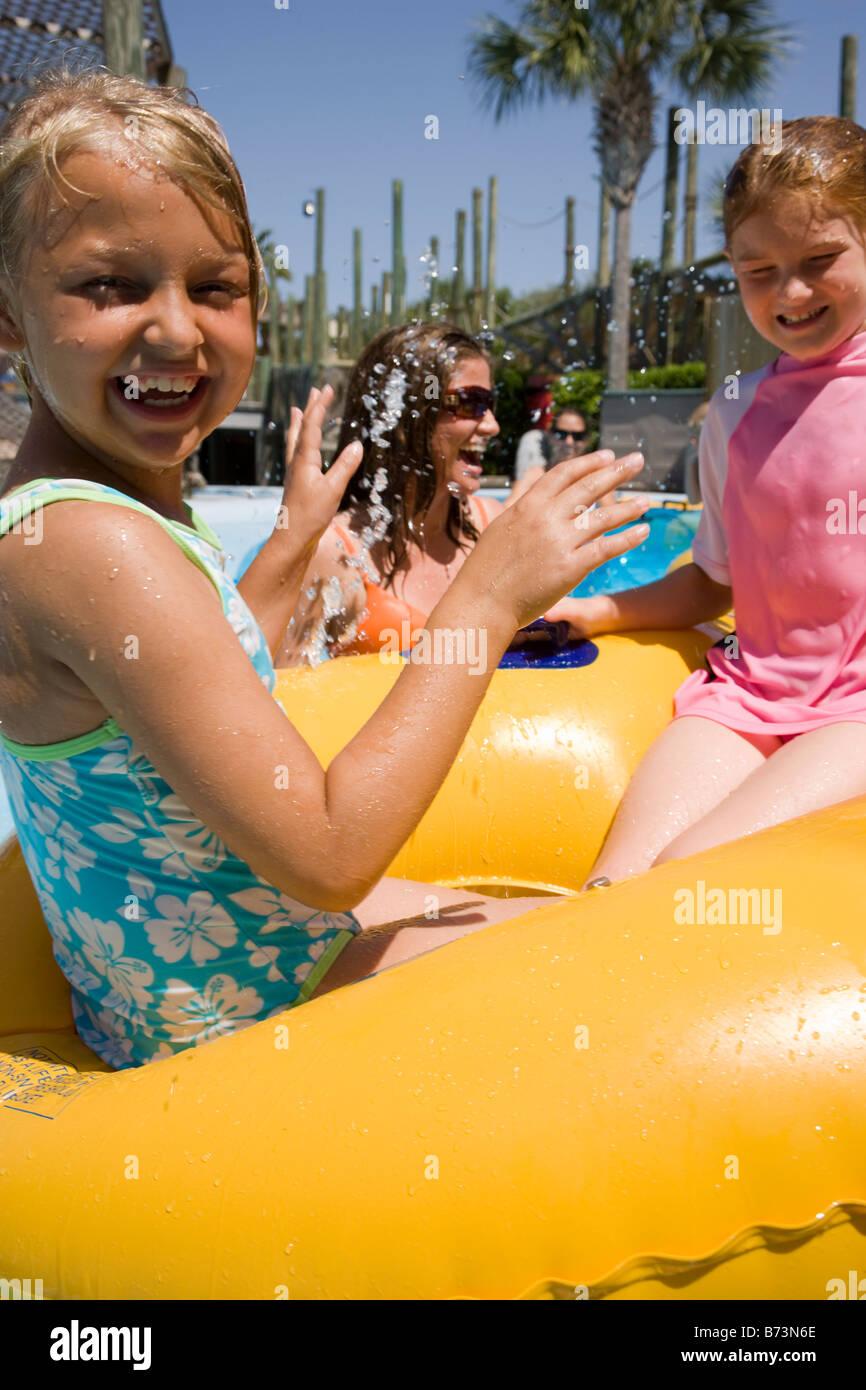 Two young girls splashing on raft at a water pak - Stock Image