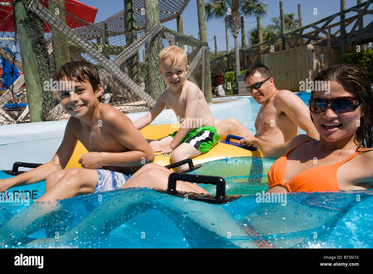 Side view of young family having fun at water park floating on innertubes Stock Photo