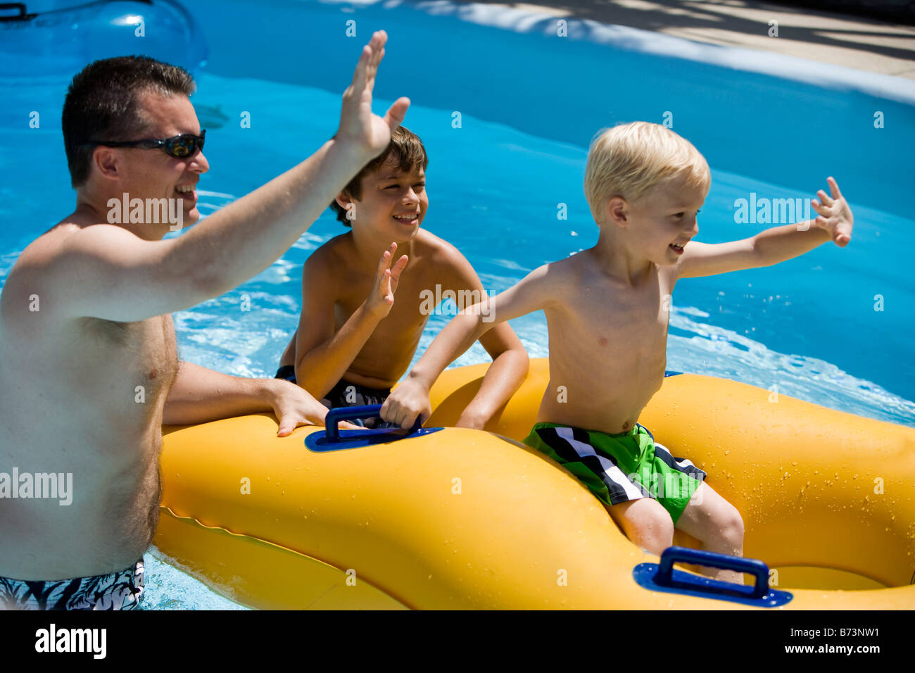 Father and sons floating on innertube at a water park Stock Photo