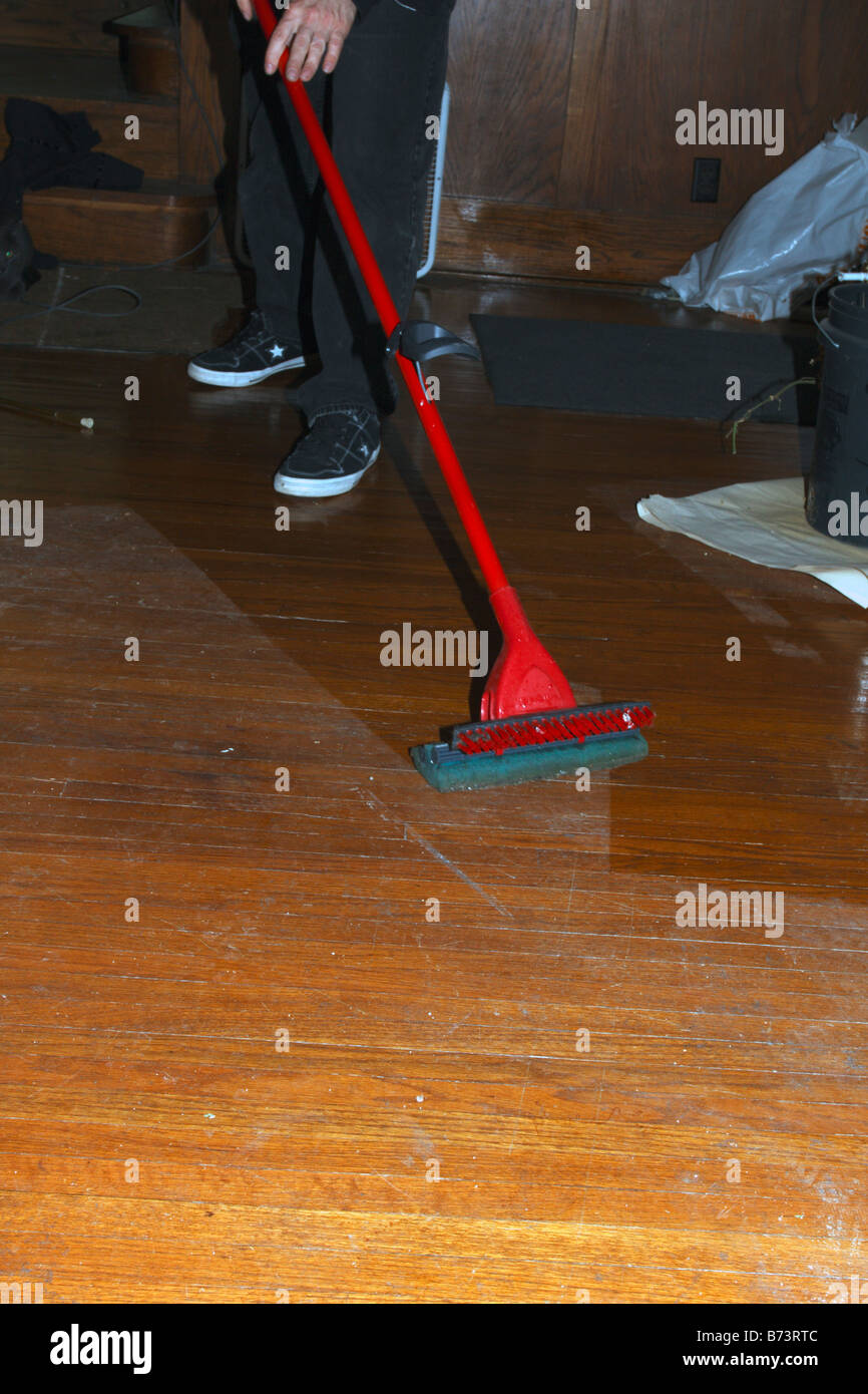 Mopping wood floor with disposable mop. - Stock Image