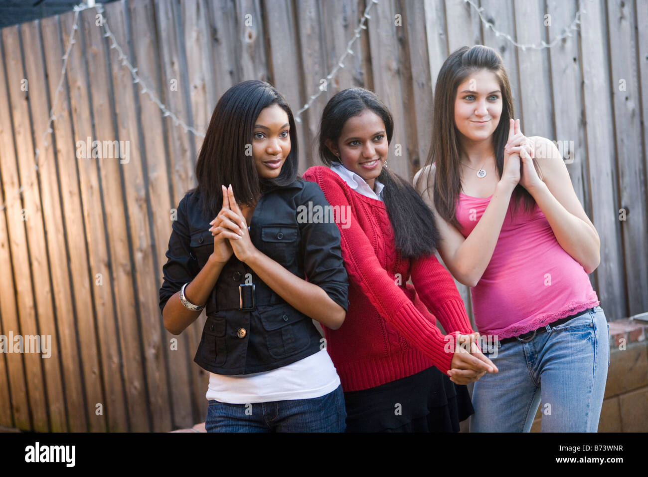 Three young multi-racial girlfriends posing - Stock Image