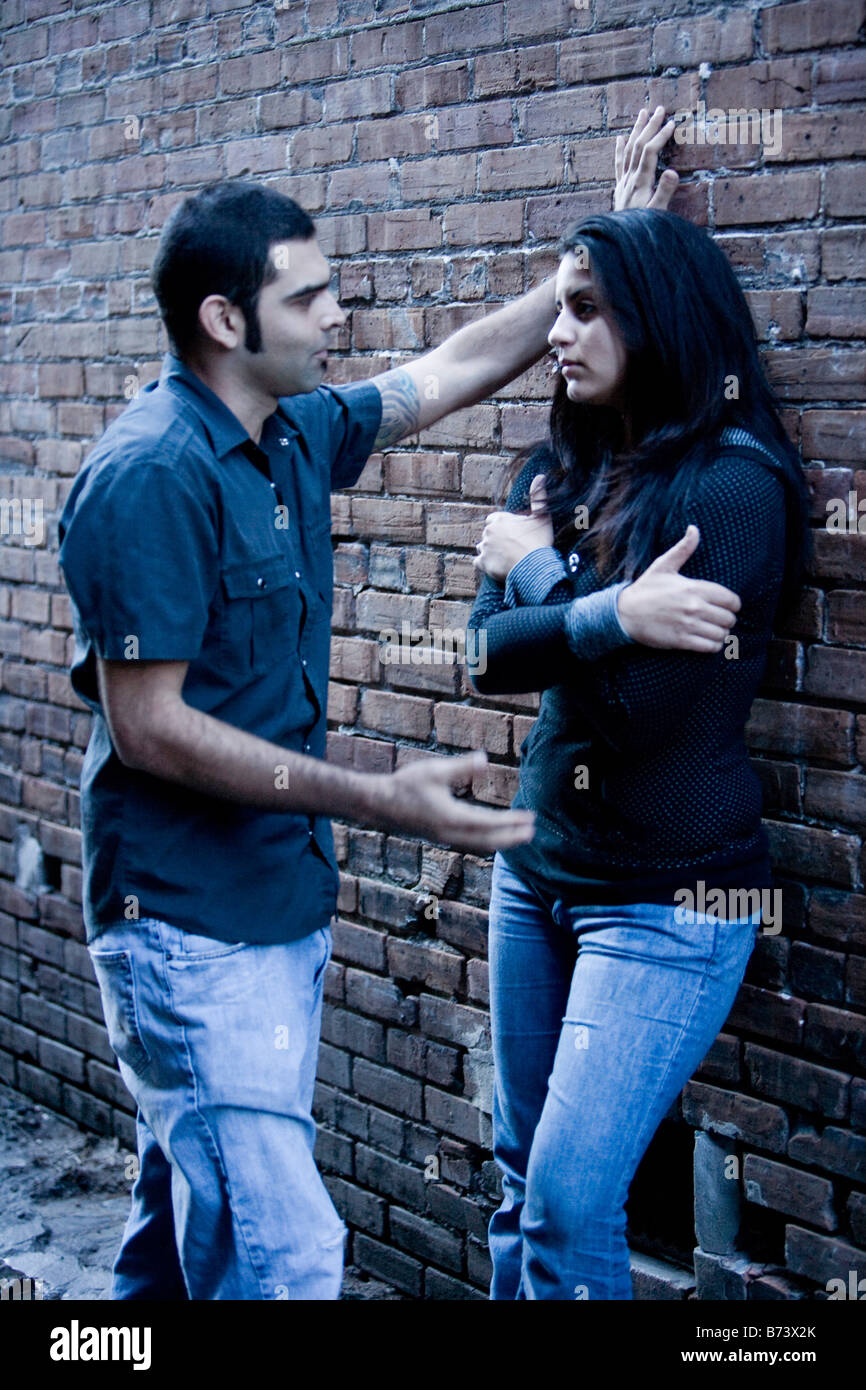 Young Hispanic couple talking outside leaning against brick wall - Stock Image