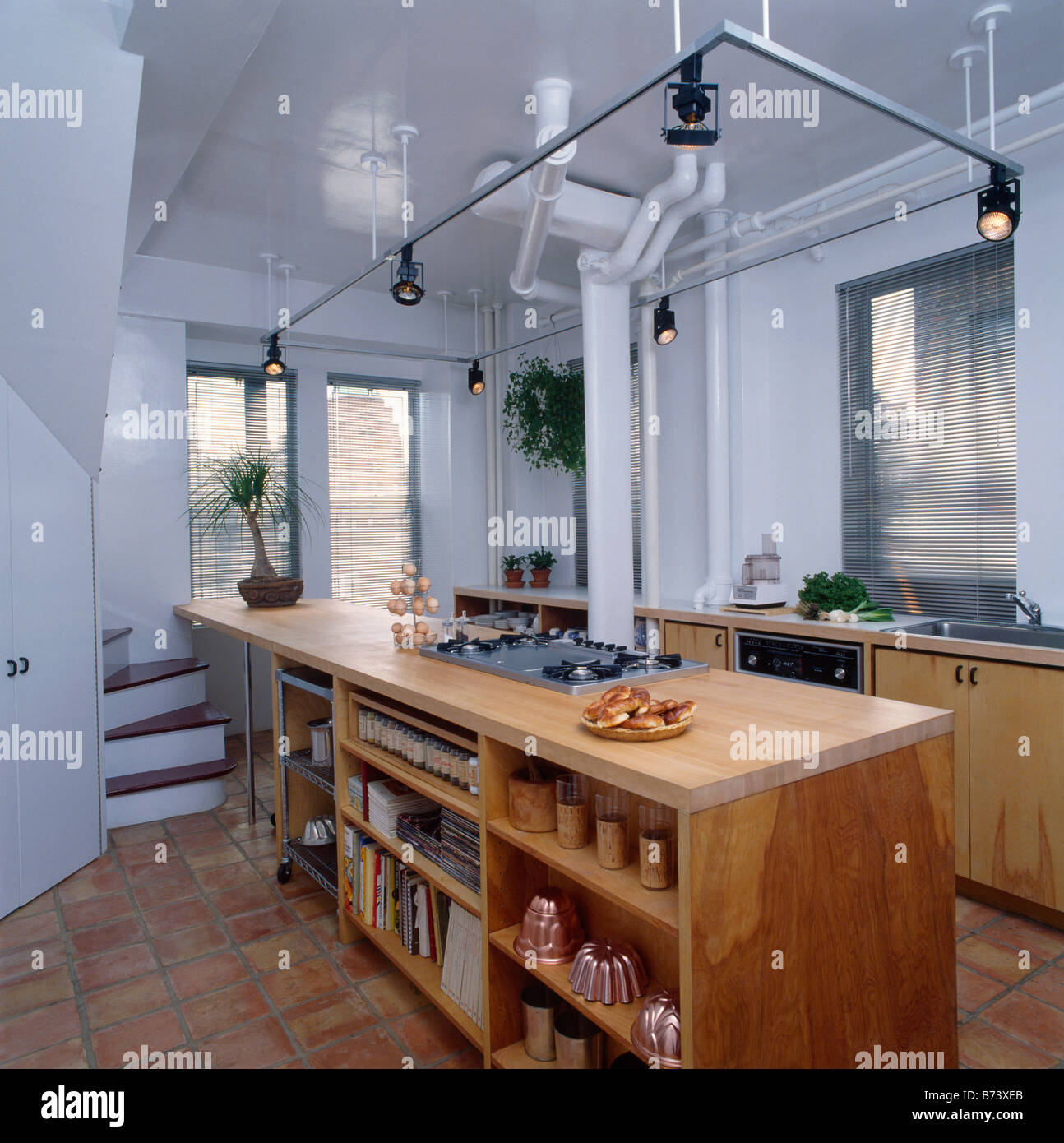 Track Lighting Above Wooden Peninsular Unit Wityh Shelving In Modern White Kitchen Stock Photo Alamy