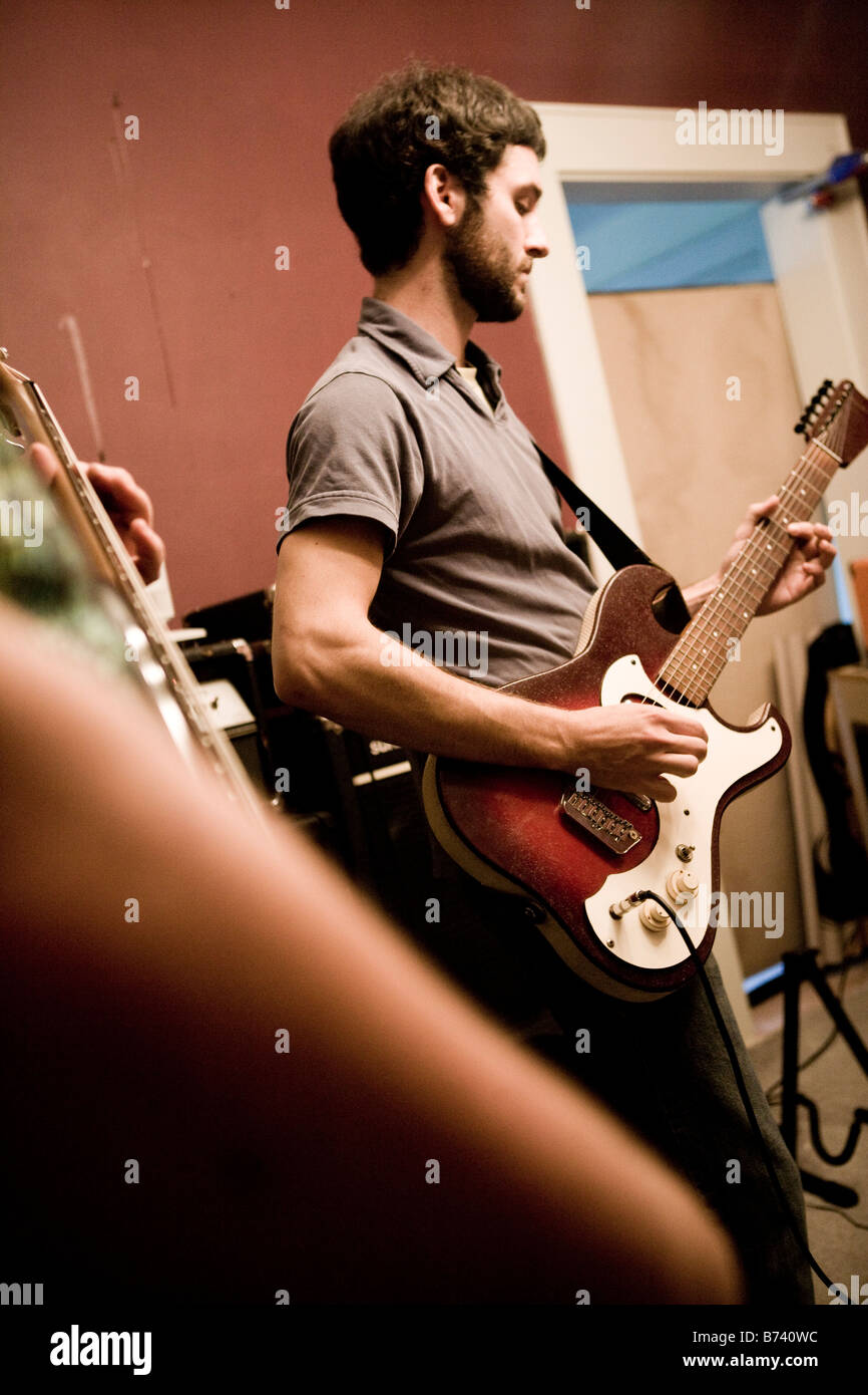 Young man playing guitar with band - Stock Image