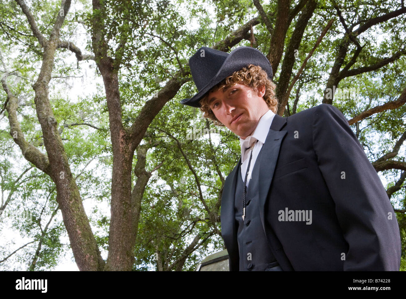 Portrait of young cowboy wearing full suit and cowboy hat outdoors - Stock Image
