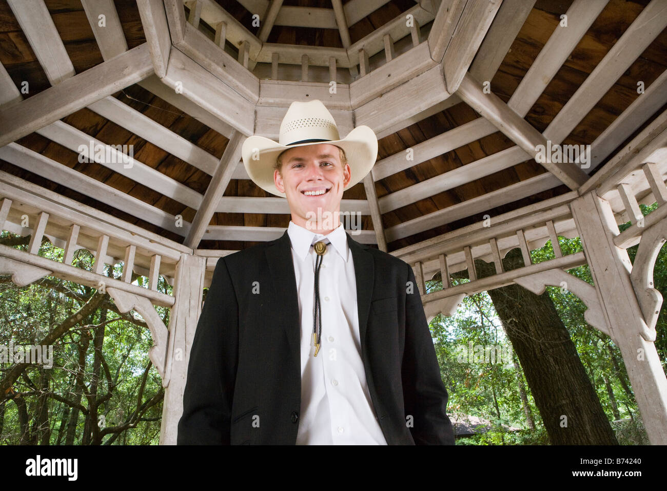 Portrait of young man in cowboy hat and suit standing in gazebo - Stock Image