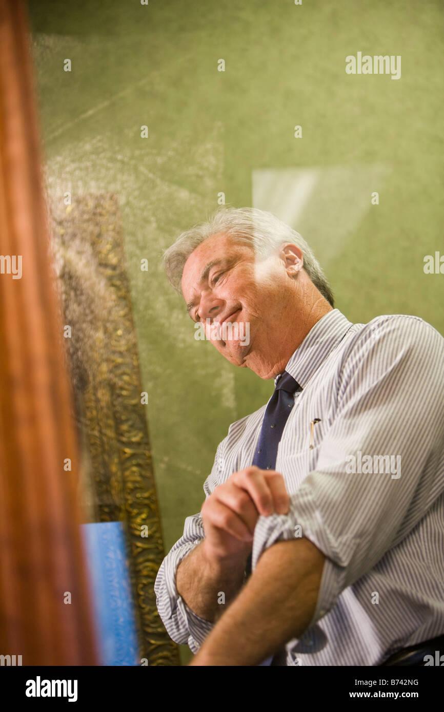 View of businessman through glass door rolling up sleeves & View of businessman through glass door rolling up sleeves Stock ...