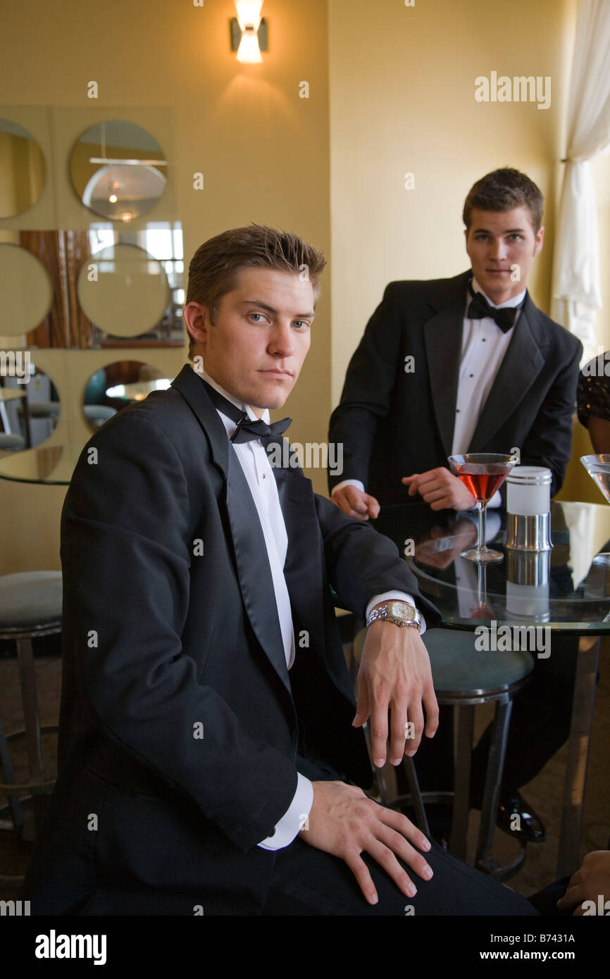 Two young adult men wearing tuxedos having drinks in restaurant lounge - Stock Image