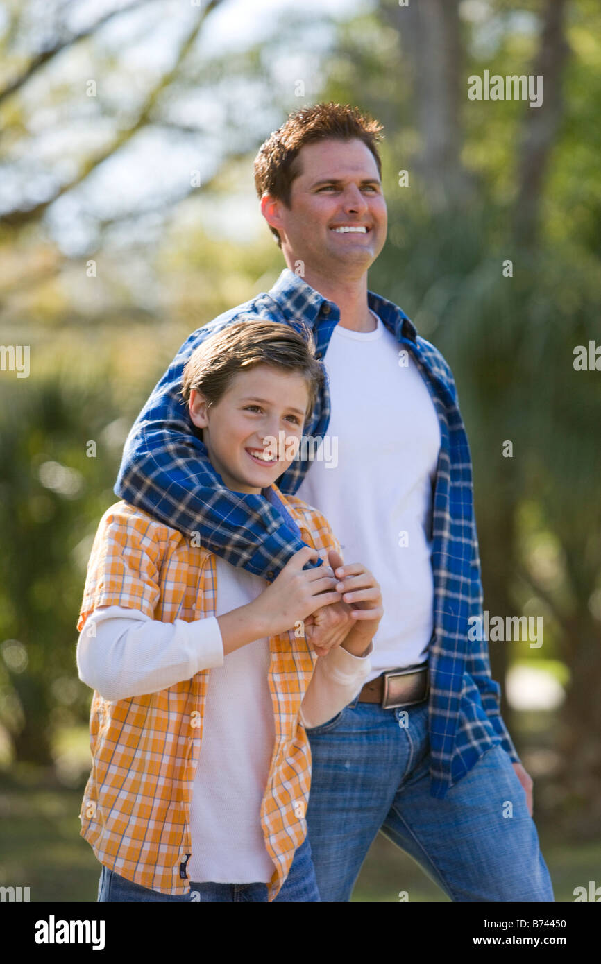2b6e62567 Father and young son standing together in park smiling Stock Photo ...