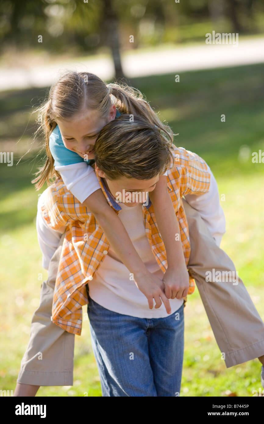 Boy giving piggyback ride to girl in park Stock Photo