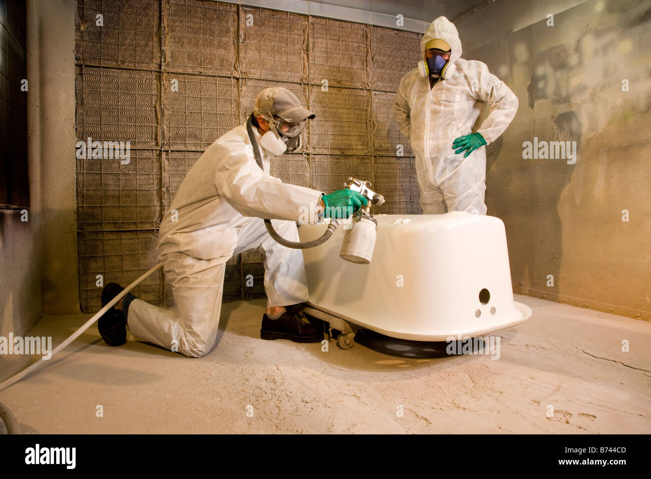 Men wearing protective gear spray painting bathtub Stock Photo ...