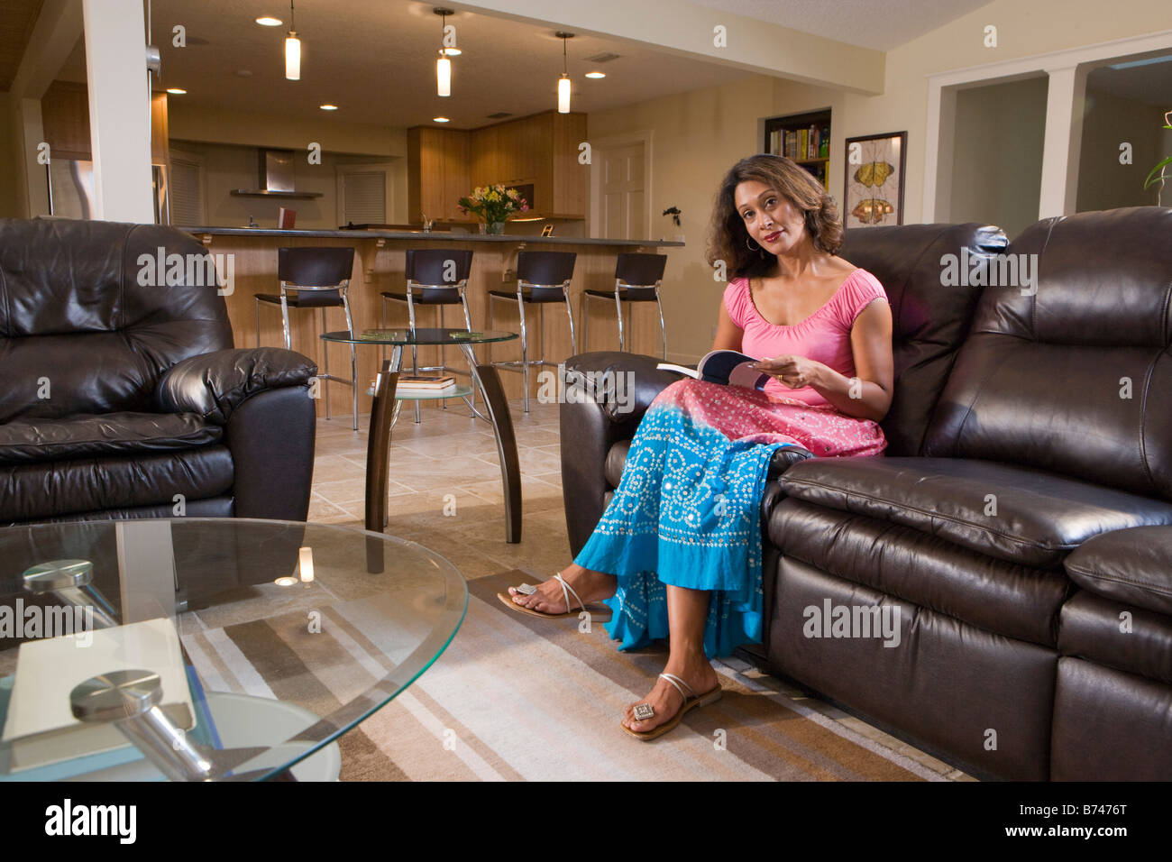 Delightful Mid Adult Indian Woman Sitting On Sofa With Book In Living Room