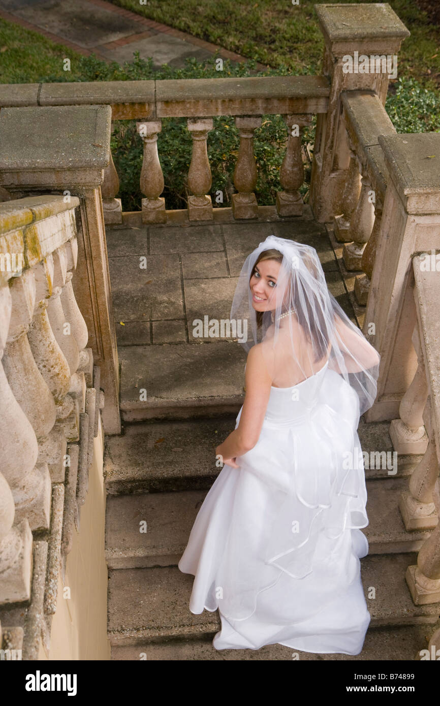 Happy young bride in wedding dress walking up stairs outdoors Stock ...