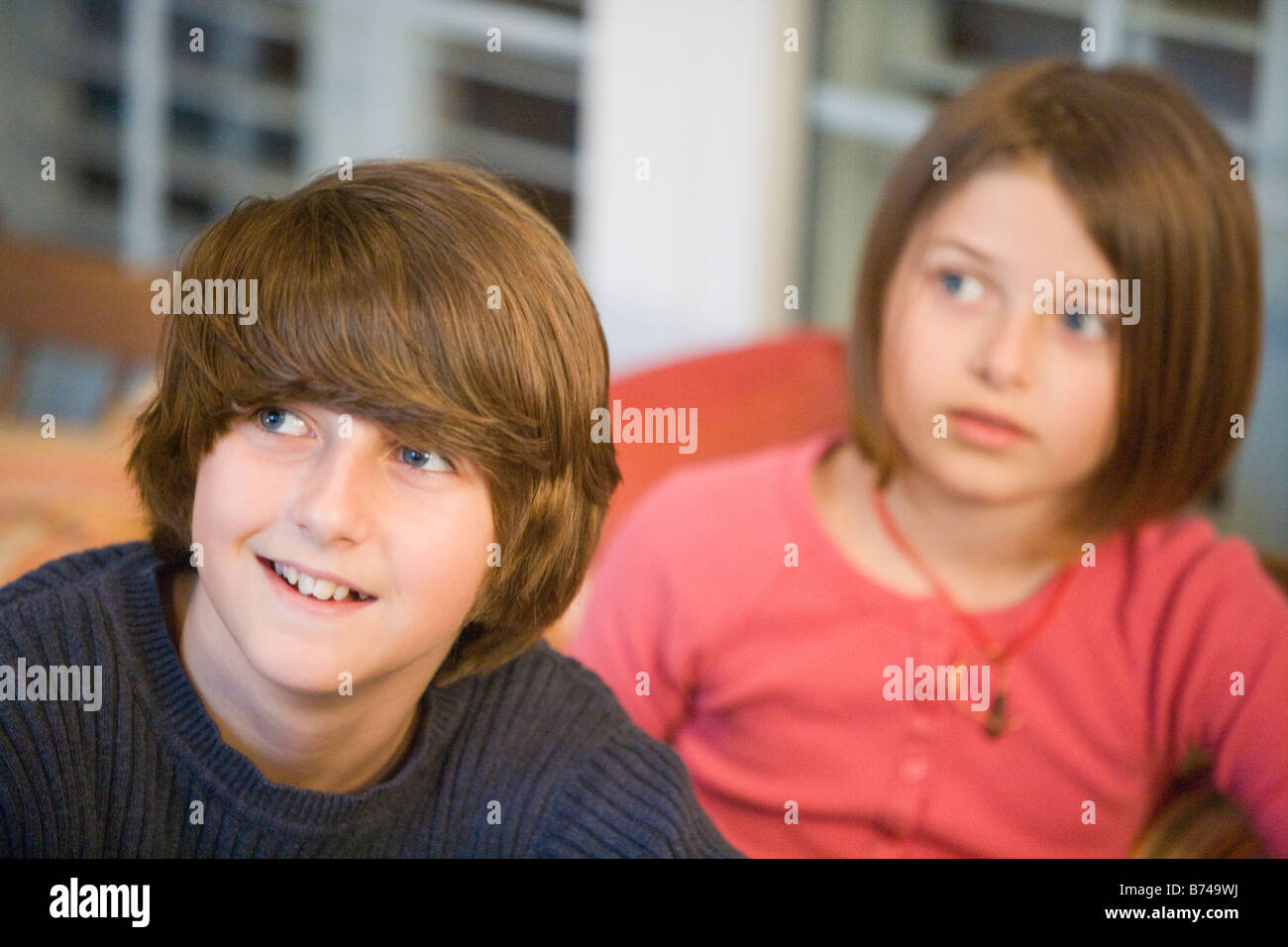 Portrait Of Brother And Sister Sitting Together On Porch