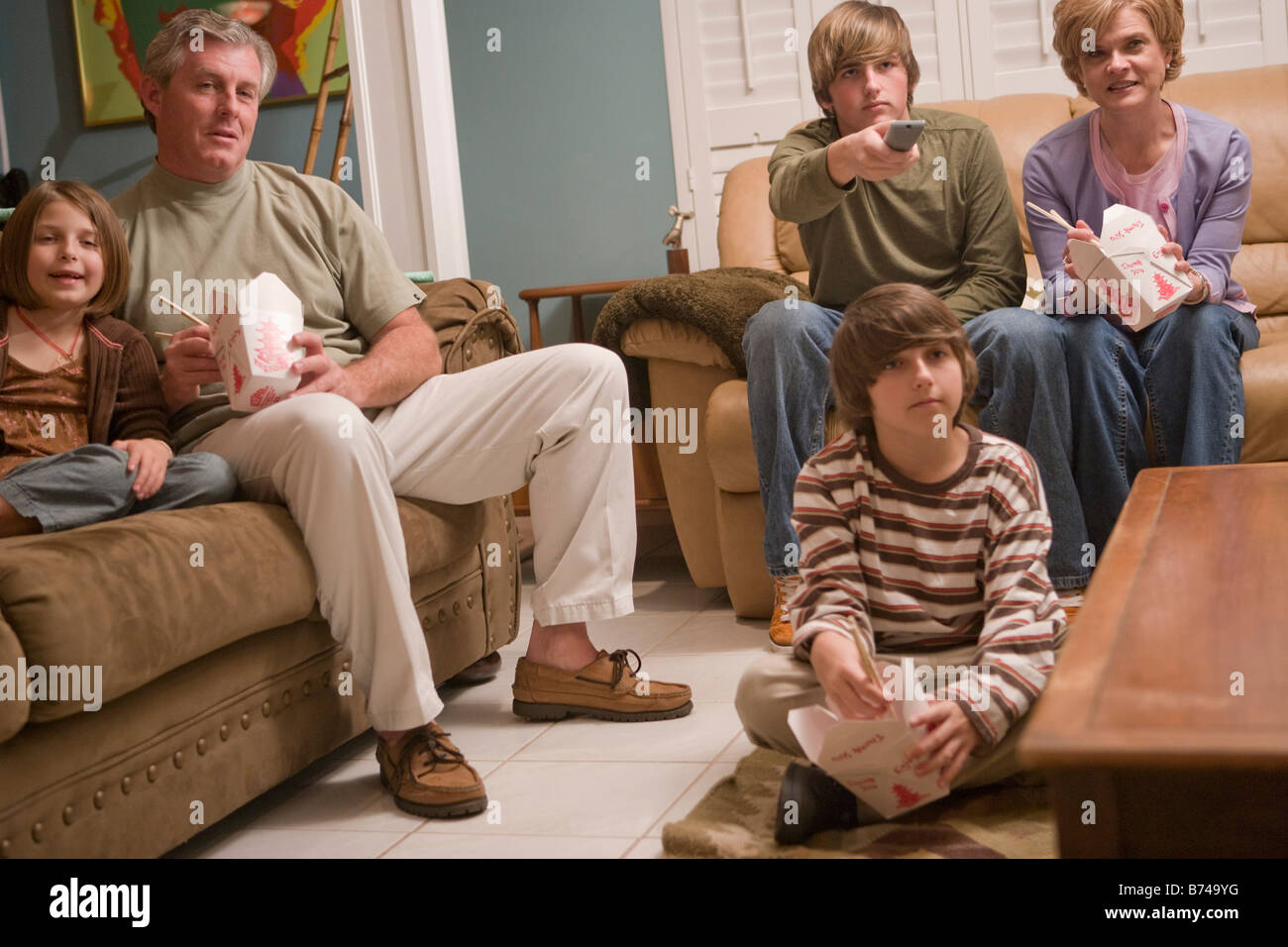 Family eating Chinese takeout dinner on couch watching TV - Stock Image