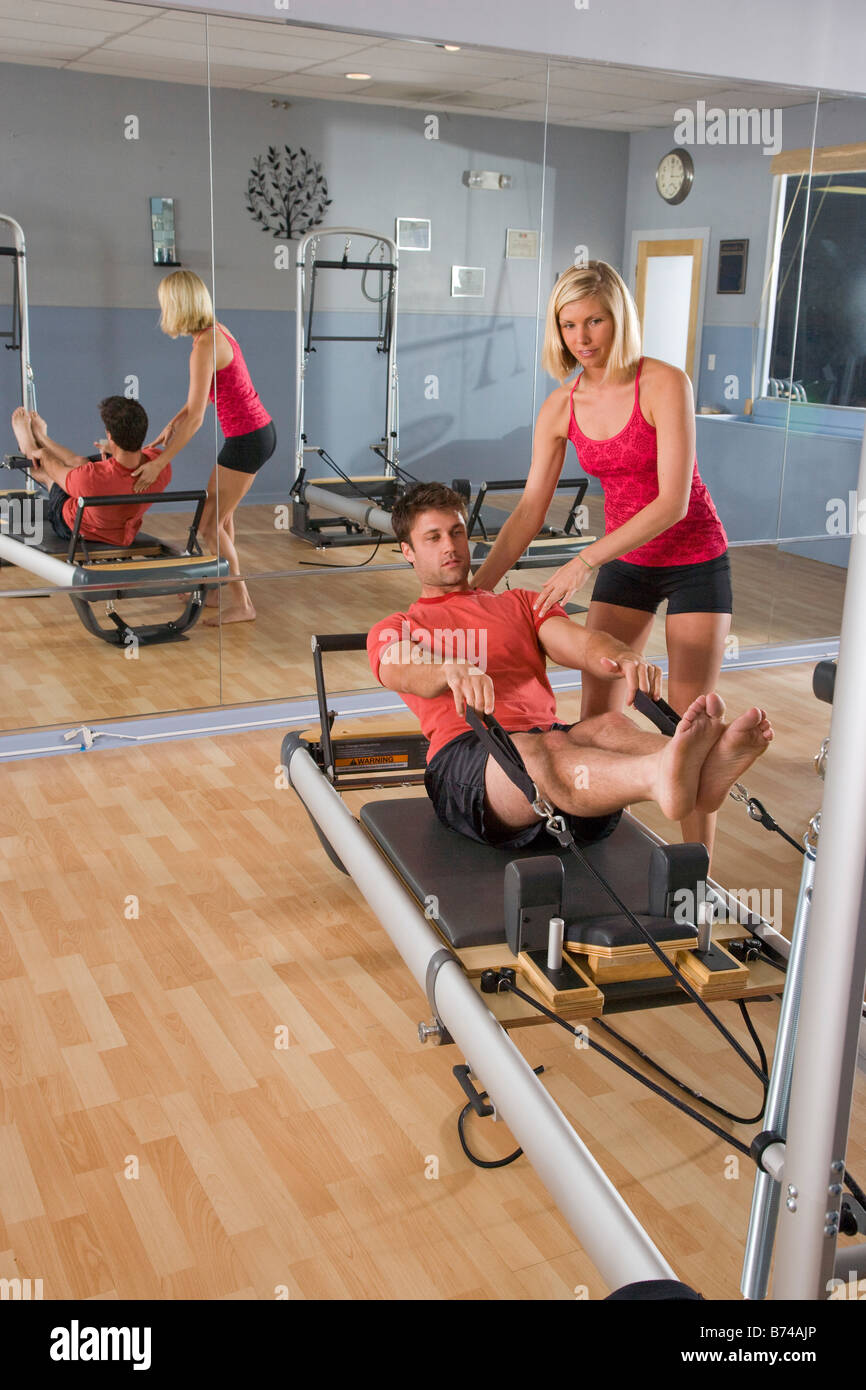 Young couple on Pilates exercise equipment in gym - Stock Image