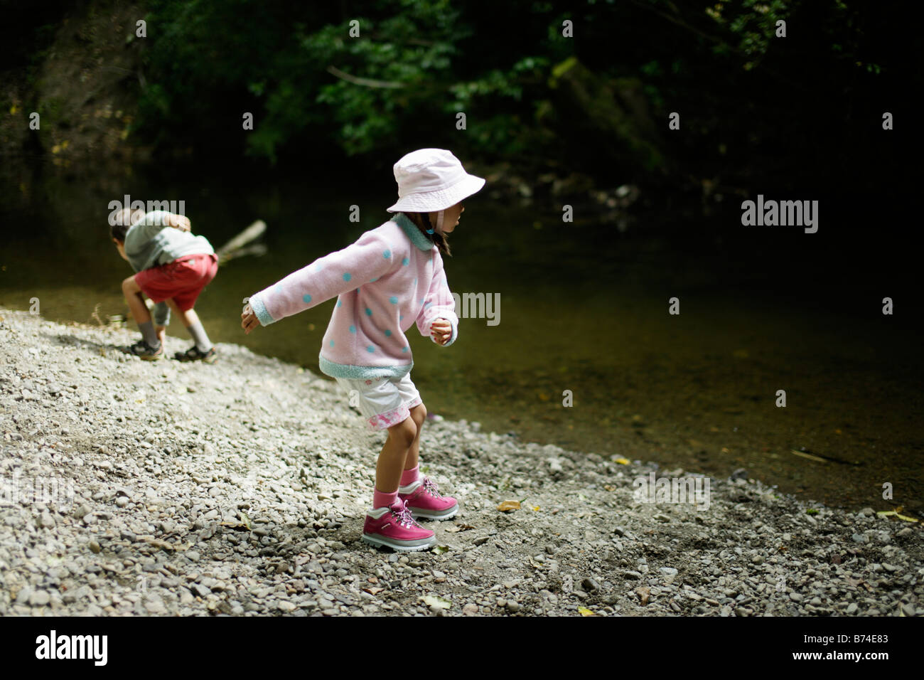 Children throw stones into stream Five year old girl and six year old brother - Stock Image