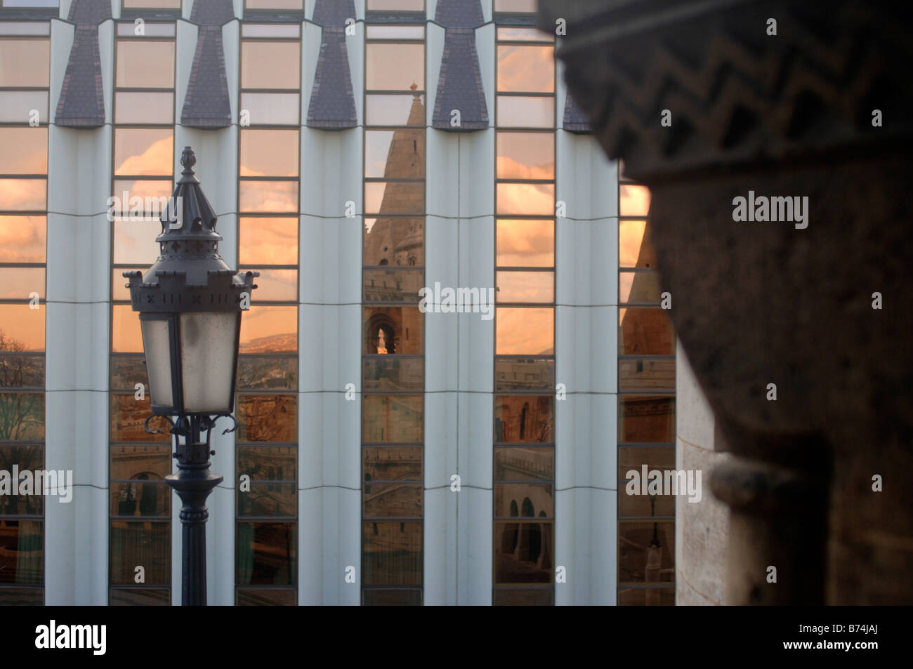 REFLECTION OF A SUNSET OVER THE FISHERMAN S BASTION IN BUDAPEST HUNGARY IN A MODERN GLASS BUILDING Stock Photo