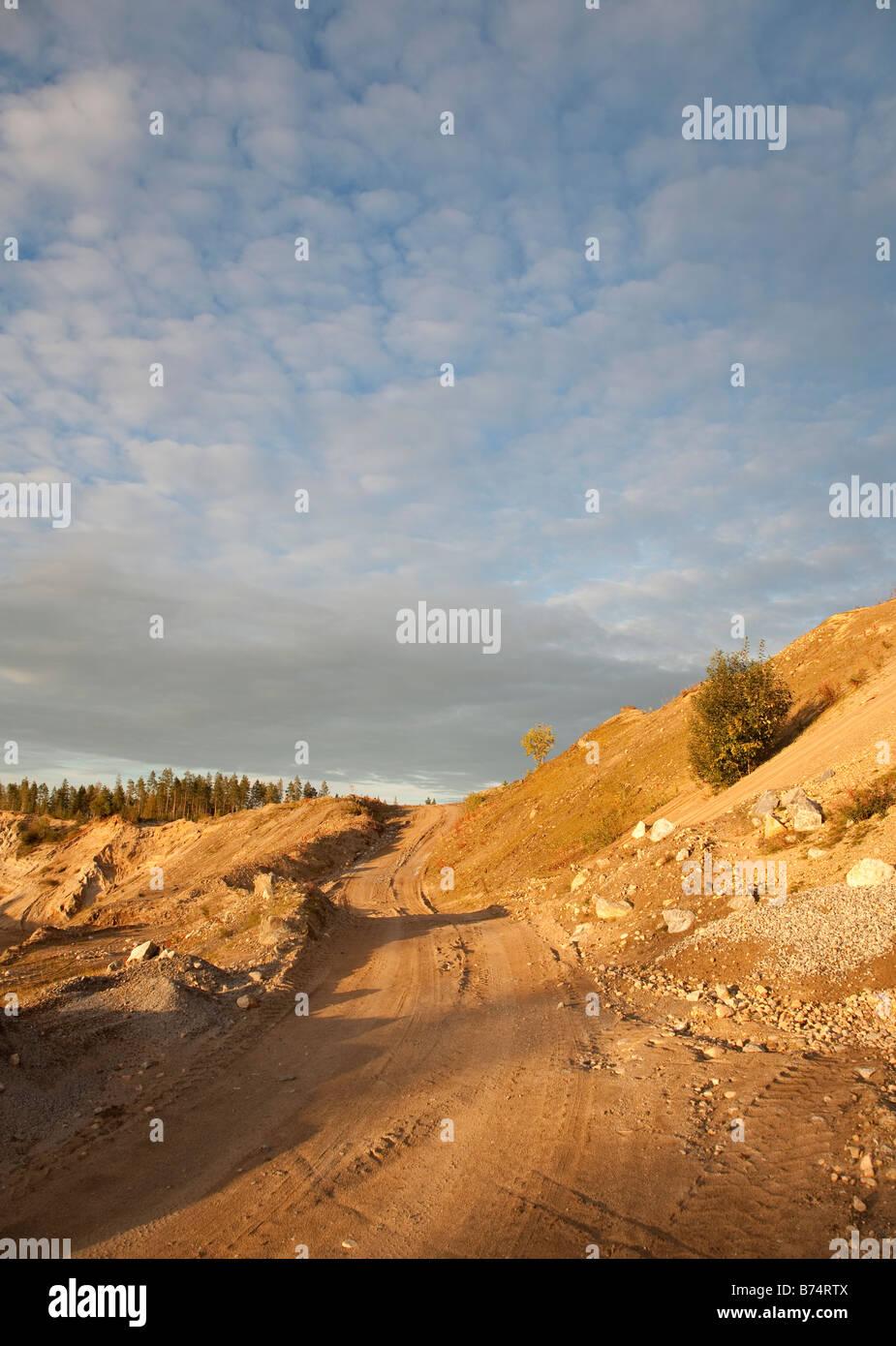 Dirt road on gravel pit slope on esker ridge - Stock Image