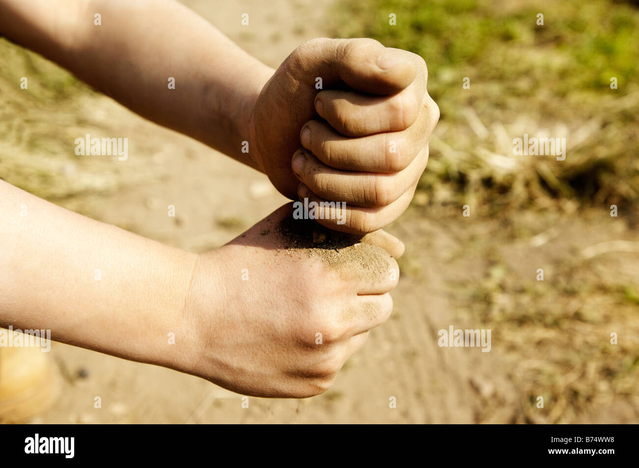 Young persons hands with dust or sand - Stock Image