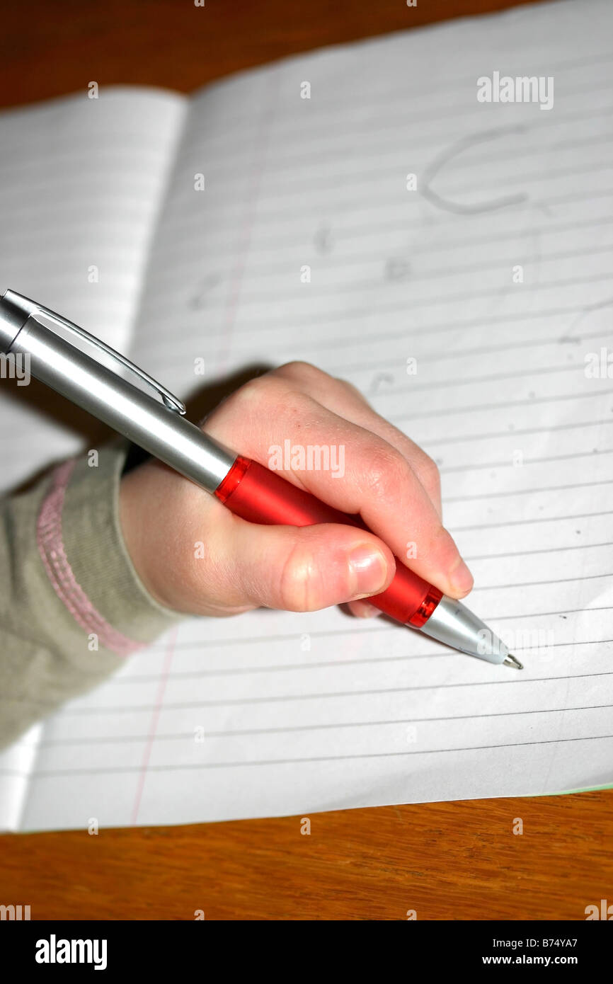 Little girl writing with left hand - Stock Image