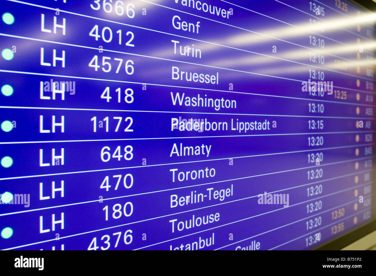 Airport flight schedule screen showing international flights with gates and departure times Frankfurt Airport Germany - Stock Image
