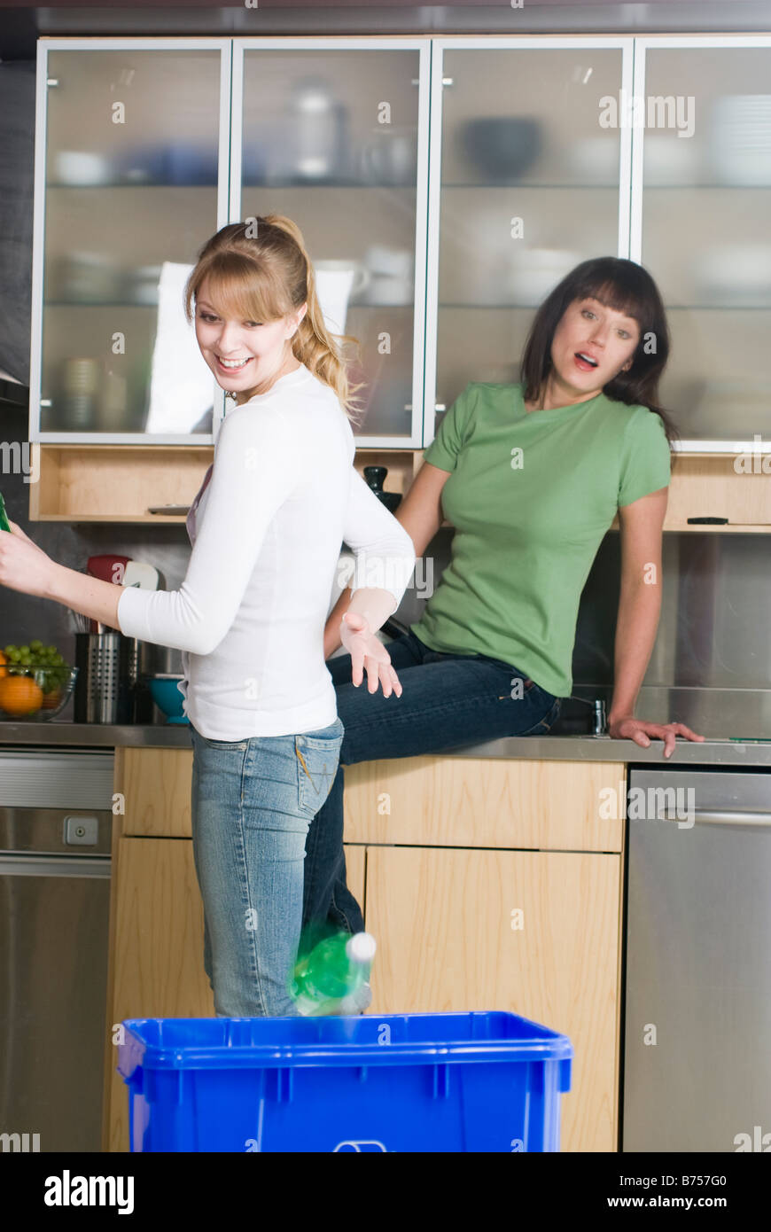 Woman tossing recycling into recycling bin as friend watches, Winnipeg, Manitoba Stock Photo