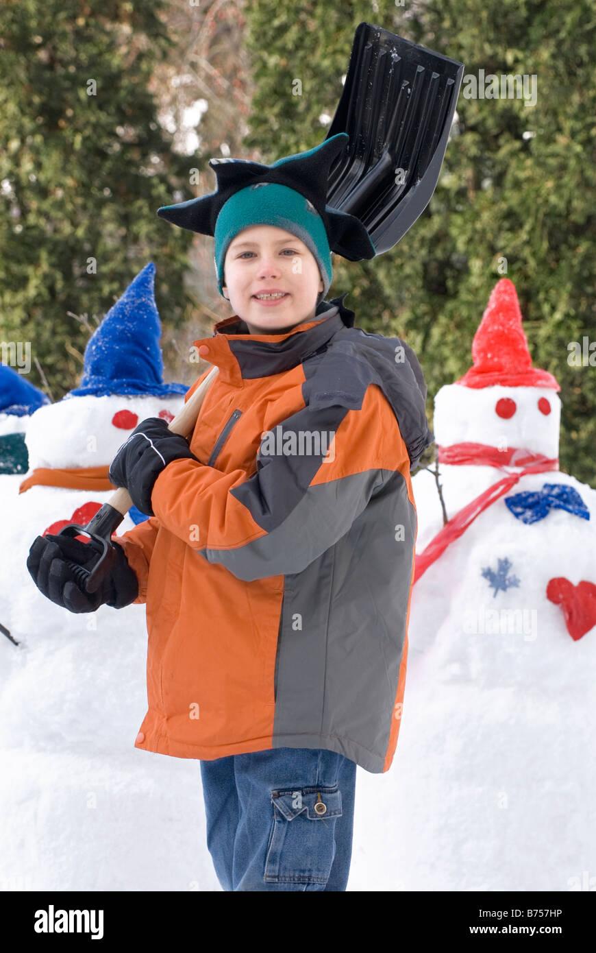 Ten year old boy with shovel beside snowmen, Winnipeg, Canada - Stock Image