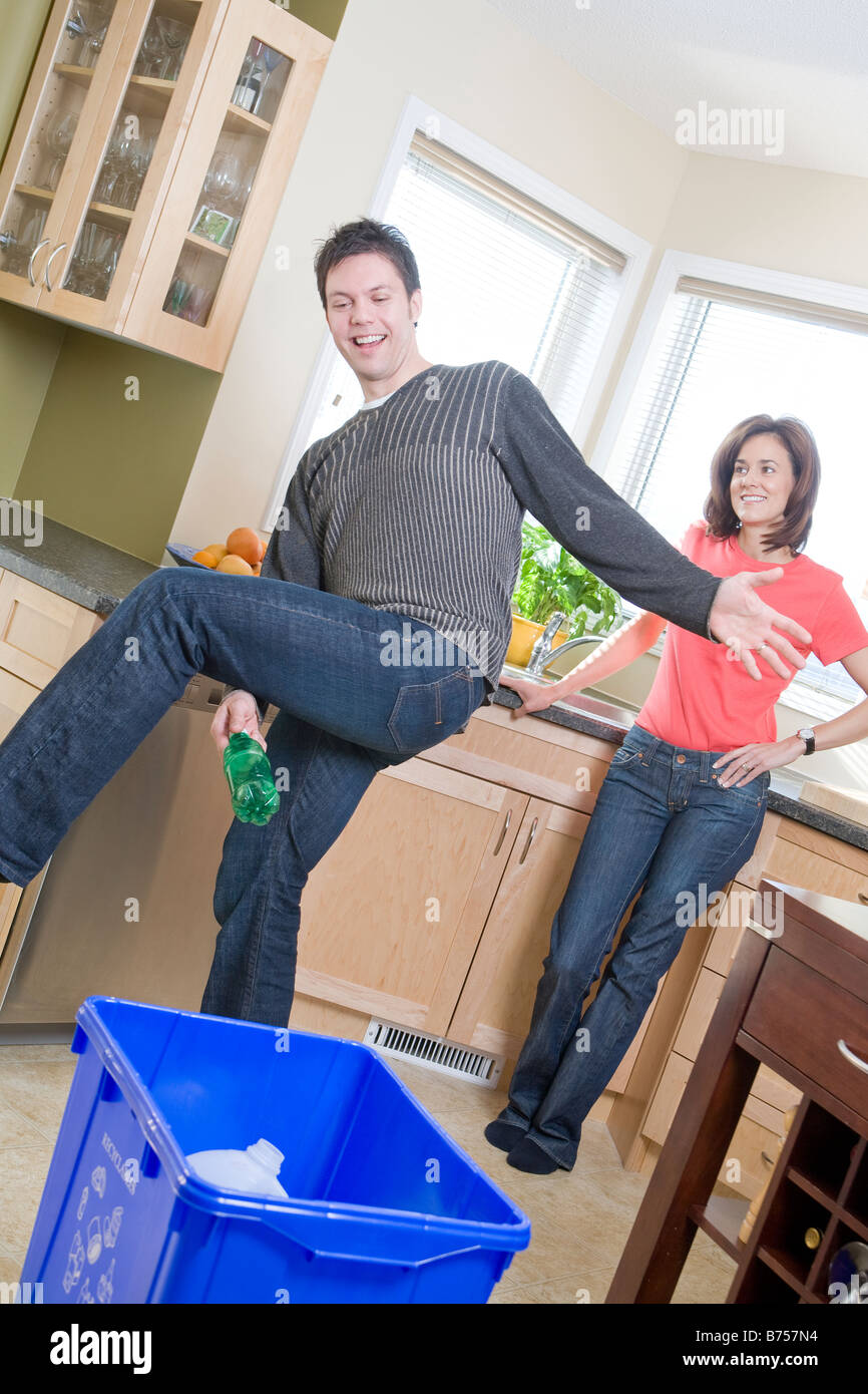 Couple laughing in kitchen as man tosses bottle into recycling bin, Winnipeg, Canada Stock Photo