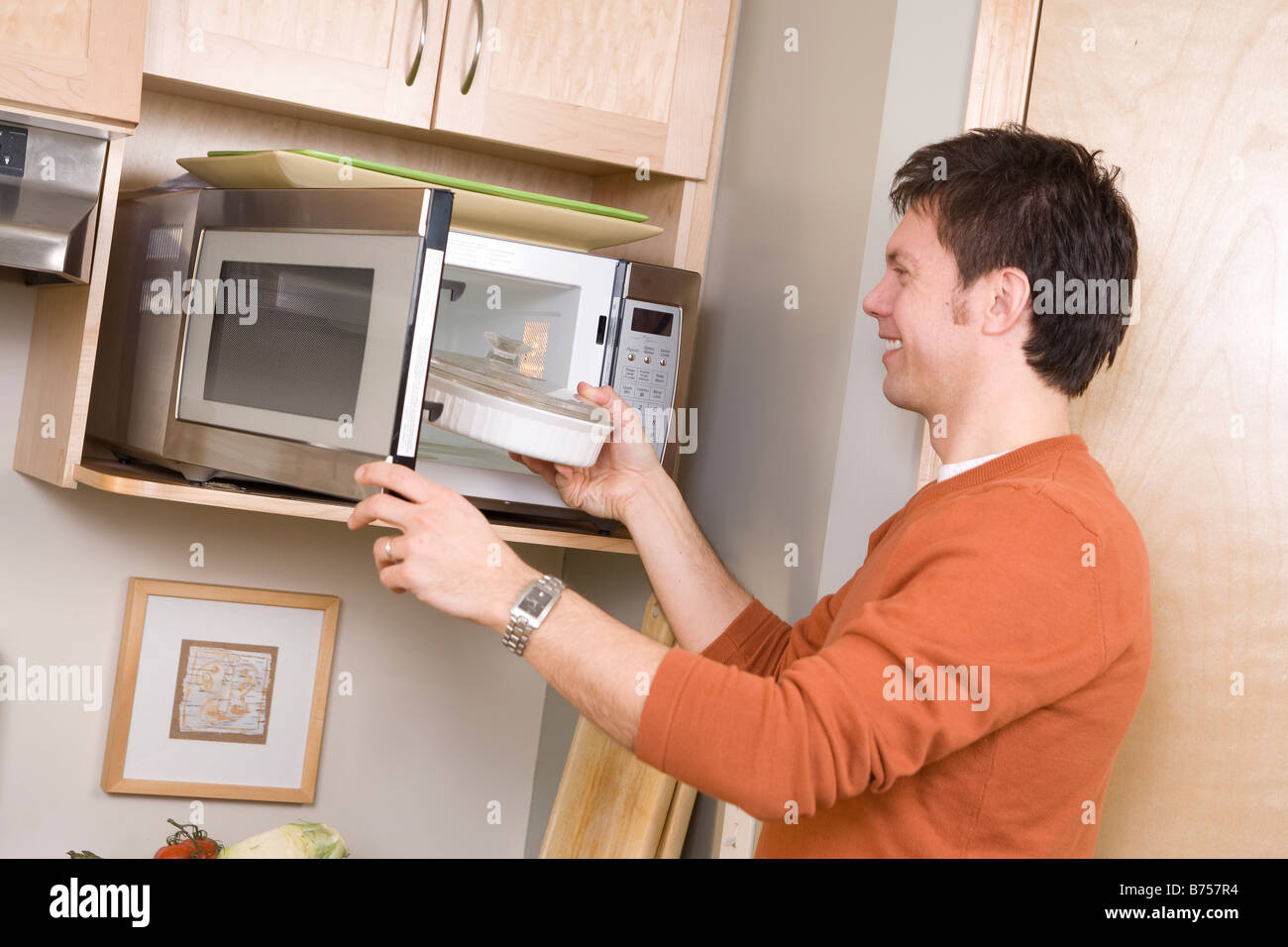 Man places glass dish in energy efficient microwave oven, Winnipeg, Canada - Stock Image