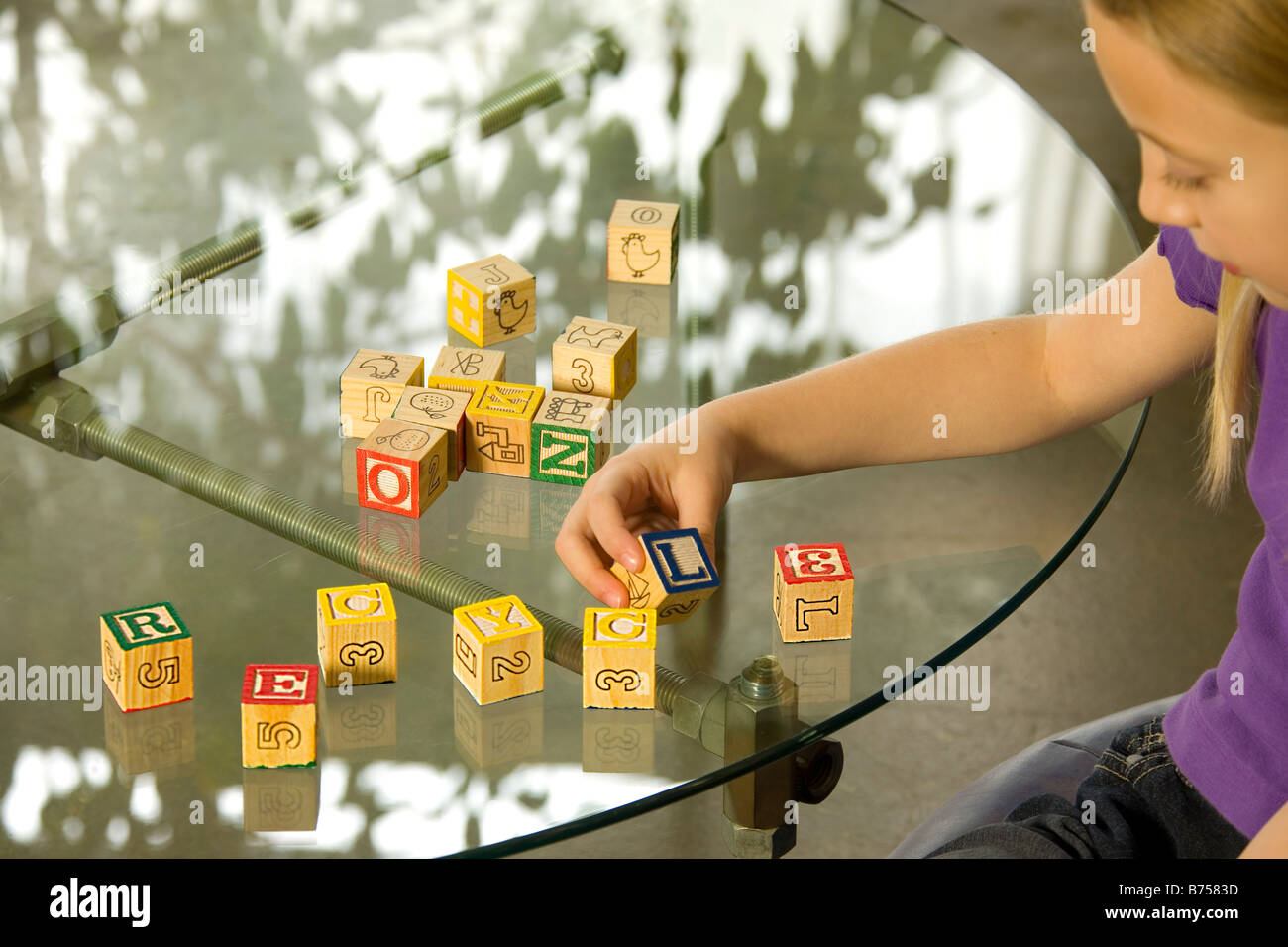 Young girl spelling recycle with alphabet blocks - Stock Image