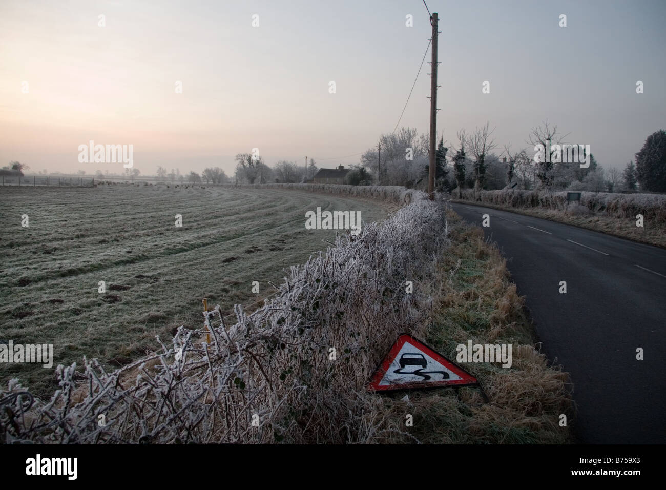 A  frosty winters morning landscape with a fallen slippery surface road sign: Somerset, UK - Stock Image