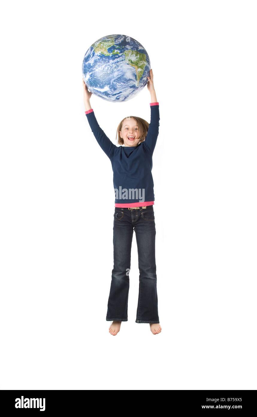 9 year old girl jumping with the globe, Winnipeg, Manitoba Stock Photo