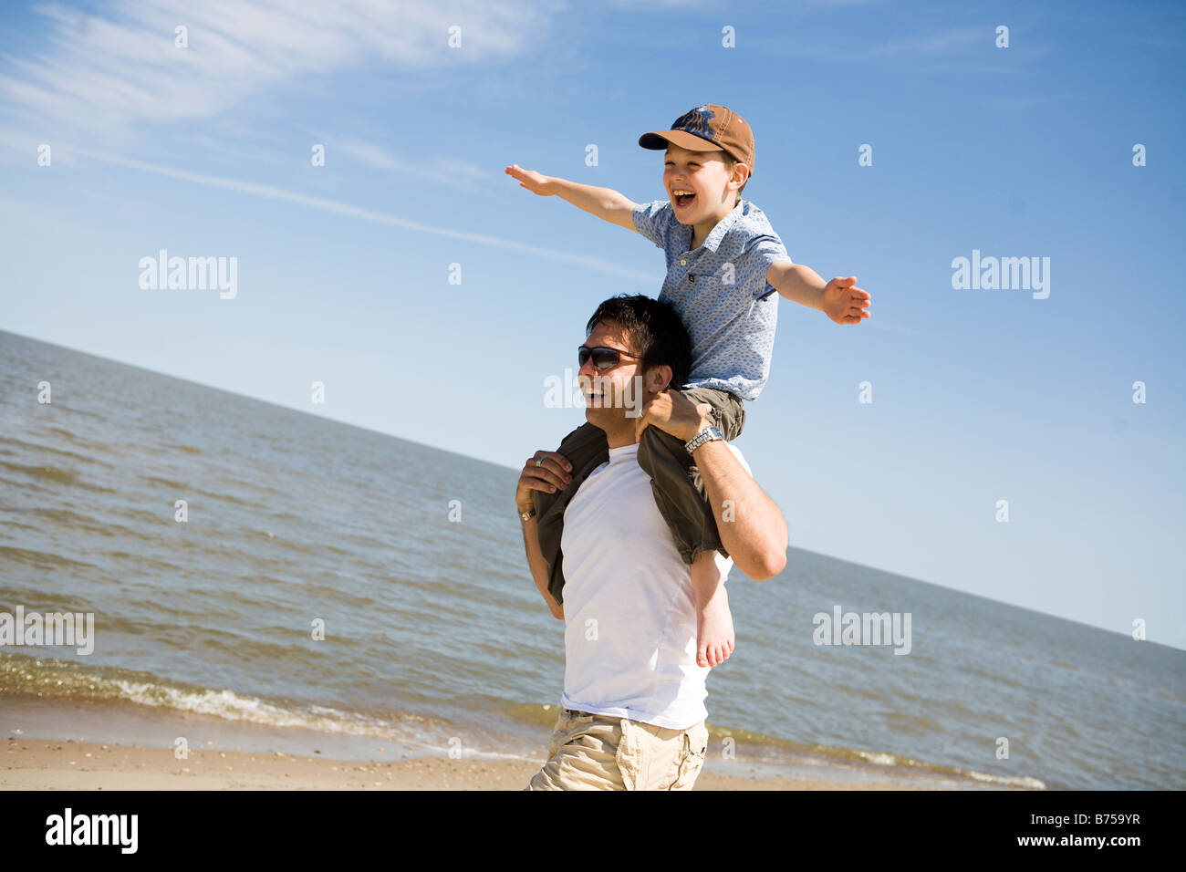 Man carries boy (7) on his shoulders, Grand Beach Provincial Park, Manitoba, Canada - Stock Image