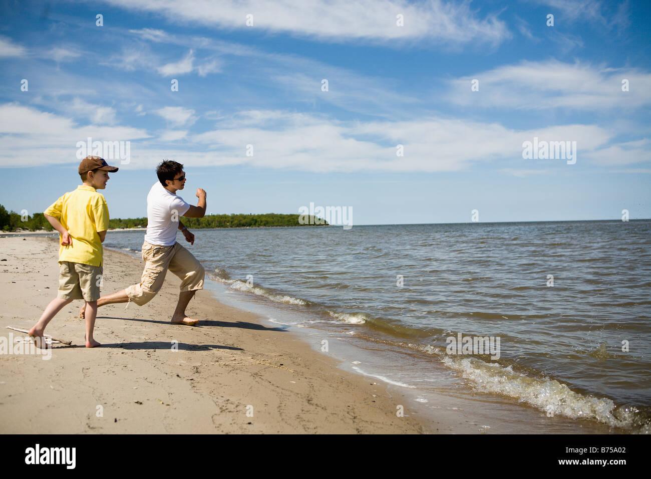Man and boy (7) skipping stones, Grand Beach Provincial Park, Manitoba, Canada - Stock Image
