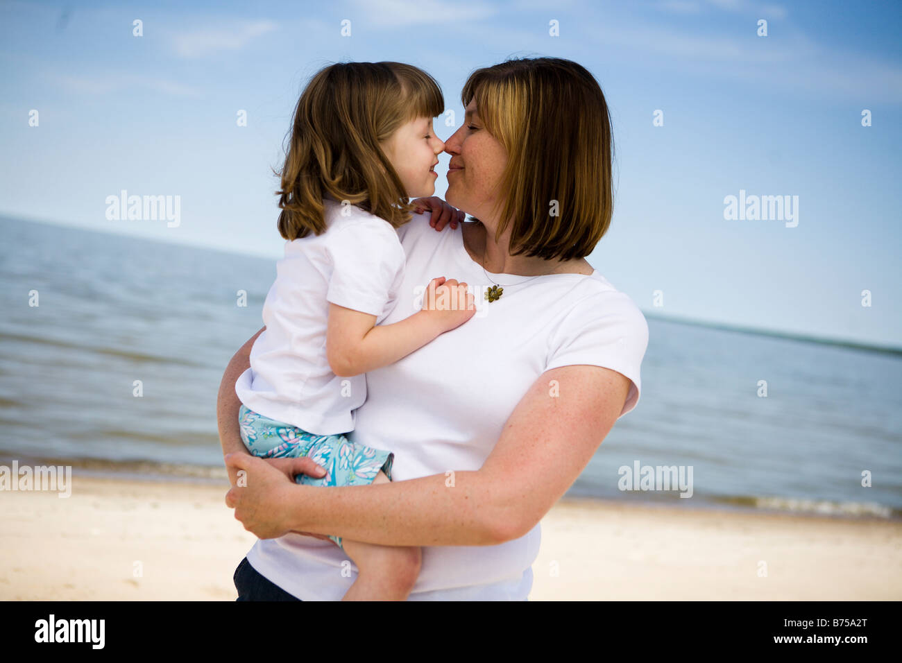 Woman and girl (4), cuddle, Grand Beach Provincial Park, Manitoba, Canada - Stock Image